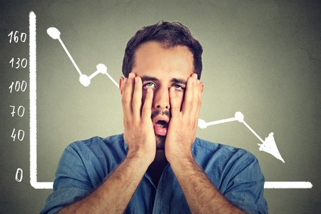 Photo pour Portrait frustrated stressed young man desperate with financial market chart graphic going down on grey office wall background. Poor economy financial crisis concept. Face expression, emotion - image libre de droit