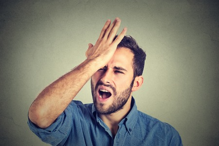 Photo for Regrets wrong doing. Closeup portrait silly young man, slapping hand on head having a duh moment isolated on gray background. Negative human emotion facial expression feeling, body language, reaction - Royalty Free Image