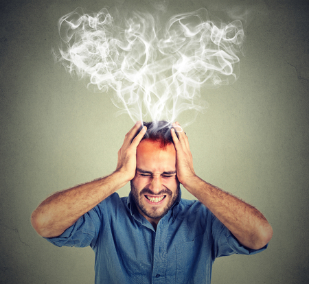 Foto de Portrait young stressed man screaming thinking too hard steam coming out up of head isolated on grey wall background. Face expression emotion perception - Imagen libre de derechos
