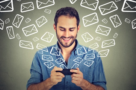 Foto de Portrait young happy man busy sending messages emails from smart phone email icons coming out flying of mobile phone isolated on gray wall background. Telecommunications, internet, data plan concept - Imagen libre de derechos