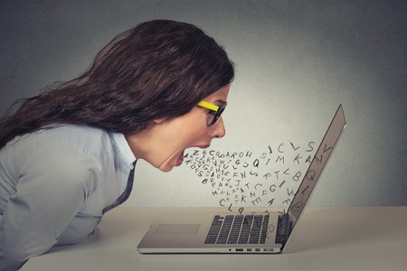 Angry furious businesswoman working on computer, screaming with alphabet letter coming out of open mouth. Negative human emotions, facial expressions, feelings, anger management issues concept