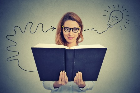 Photo pour Woman in glasses reading big book comes up with an idea - image libre de droit