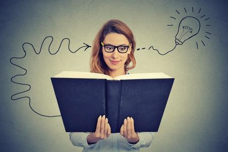 Photo pour Woman in glasses reading big book comes up with an idea - image libre de droit