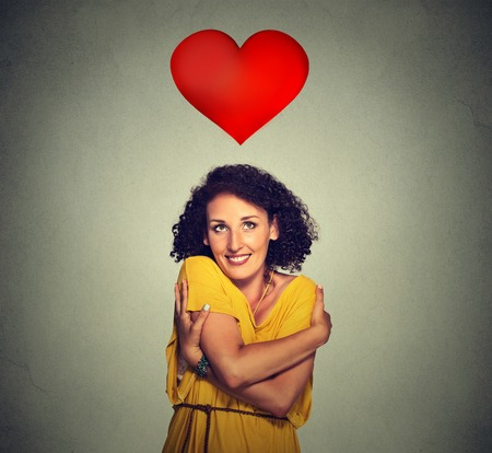 Photo for Closeup portrait smiling woman holding hugging herself with red heart above head isolated gray wall background. Positive human emotion, facial expression feeling, attitude. Love yourself concept - Royalty Free Image