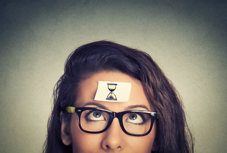 Photo pour Time management concept young woman with sand clock sign sticker on her forehead - image libre de droit