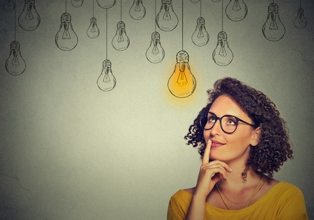 Photo for Portrait thinking woman in glasses looking up with light idea bulb above head isolated on gray wall background - Royalty Free Image