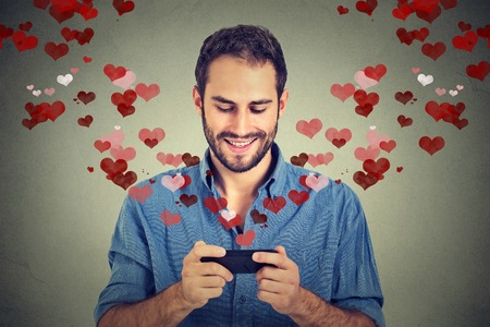Photo for Portrait happy man sending love sms text message on mobile phone with red hearts flying away from screen isolated on grey wall background. Human emotions - Royalty Free Image