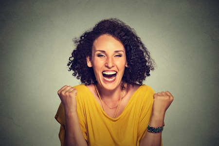 Photo pour happy woman exults pumping fists ecstatic celebrates success on gray background - image libre de droit