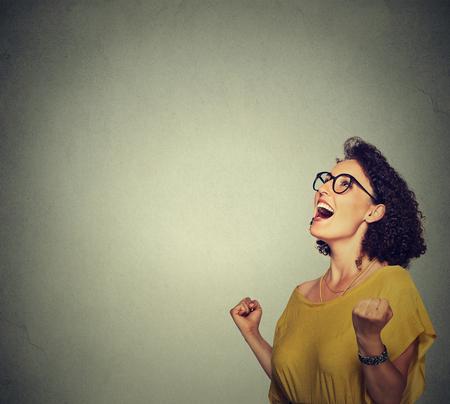 Photo pour portrait happy woman in yellow dress exults pumping fists ecstatic celebrates success - image libre de droit