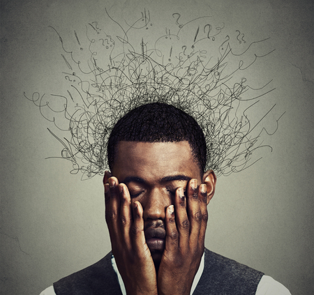 Foto de Depressed worried young man with worried desperate stressed expression hands covering face and brain melting into lines question marks. Depression, anxiety disorders, life failure. Gray background - Imagen libre de derechos