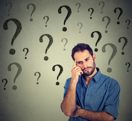 Foto de Thinking handsome young business man wondering looking down has many questions isolated on gray wall background with many question marks. Thinking guy - Imagen libre de derechos