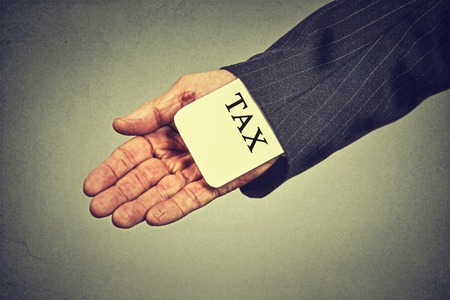 Photo pour Corruption illegal criminal activity tax evasion economy ponzi scheme concept. Closeup man hand hiding tax card in a sleeve of a suit isolated on gray wall background - image libre de droit