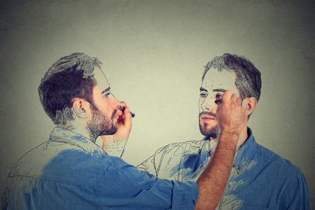 Foto de Create yourself concept. Good looking young man drawing a picture, sketch of himself on grey wall background. Human face expressions, creativity - Imagen libre de derechos