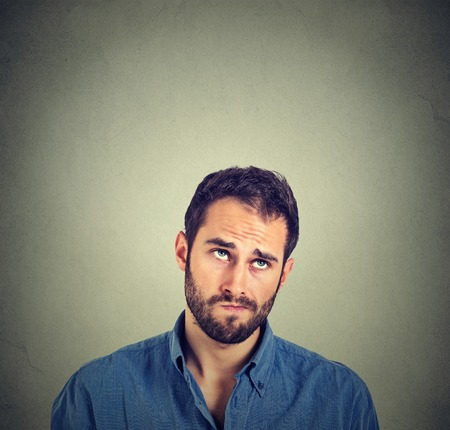 Foto de Portrait closeup funny confused skeptical man thinking looking up isolated on gray wall background with copy space above head. Human face expressions, emotions, feelings, body language - Imagen libre de derechos