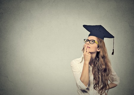 Foto de Portrait closeup beautiful thoughtful graduate graduated student girl young woman in cap gown looking up thinking isolated gray wall background. Graduation ceremony future career concept - Imagen libre de derechos