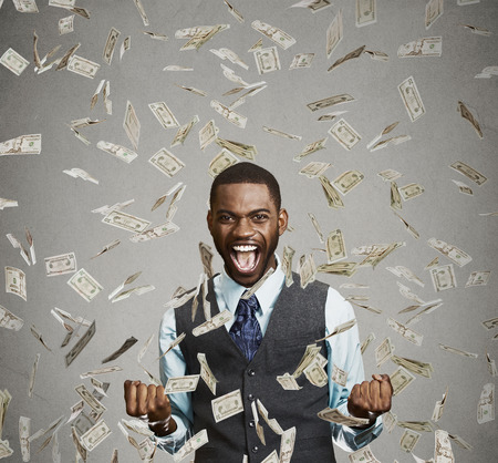 Foto de Portrait happy man exults pumping fists ecstatic celebrates success screaming under money rain falling down dollar bills banknotes isolated gray background with copy space. Financial freedom concept - Imagen libre de derechos