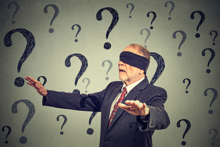 Foto de Portrait business man blindfolded stretching his arms out walking through many questions isolated on gray wall background - Imagen libre de derechos