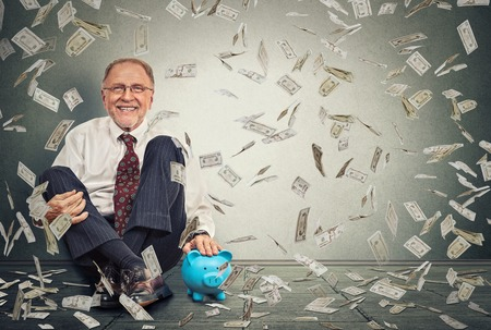 Photo for Excited happy senior man sitting on a floor with piggy bank under a money rain isolated on gray wall background. Positive emotions financial success luck good economy concept - Royalty Free Image
