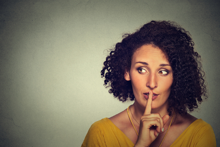 Photo pour Closeup portrait secretive young woman placing finger on lips asking shh, quiet, silence looking sideway isolated gray background. Human face expressions, sign emotion feeling body language reaction - image libre de droit