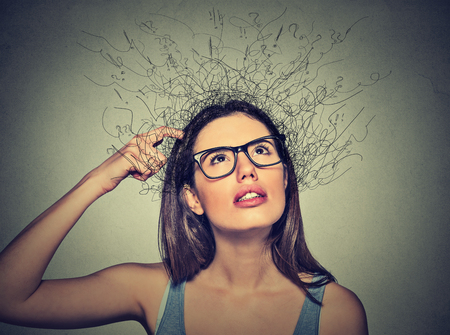 Foto de Closeup portrait young woman scratching head, thinking daydreaming with brain melting into lines question marks looking up isolated on gray background. Human facial expressions, emotion feeling sign - Imagen libre de derechos