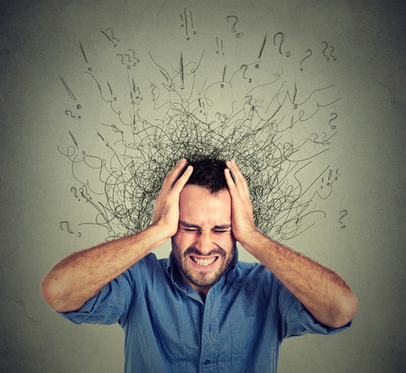 Foto de Stressed man upset frustrated has too many thoughts with brain melting into lines question marks. Obsessive compulsive, adhd, anxiety disorder. Negative human emotions face expression feelings - Imagen libre de derechos