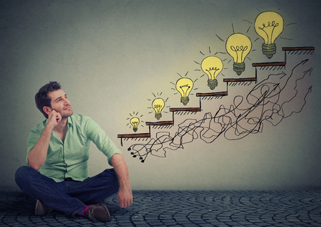 Foto de Happy man sitting on a floor in his office dreaming of business education success, promotion, company growth isolated gray wall texture background. Handsome guy looking up at growing up light bulbs - Imagen libre de derechos