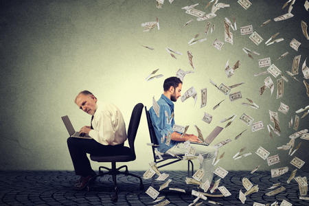 Photo for Employee compensation economy concept. Senior man working on laptop sitting next to young entrepreneur guy using computer under money rain. Pay difference concept. - Royalty Free Image