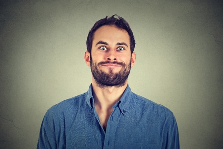 Crazy looking man making funny faces isolated on gray wall background