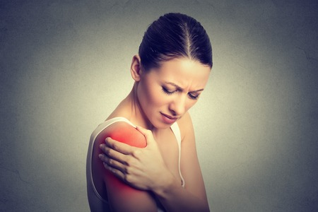 Photo pour Injured joint. Young woman patient in pain having painful shoulder colored in red. Medicine and health care concept. Gray background - image libre de droit