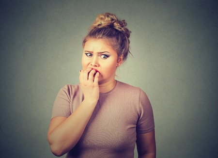 Photo for Closeup portrait nervous stressed young woman student biting fingernails looking anxiously craving something isolated on gray wall background. Human emotion face expression feeling reaction - Royalty Free Image