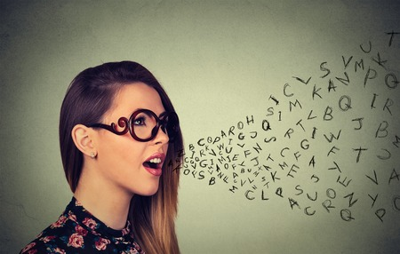 Photo pour Woman in glasses talking with alphabet letters coming out of her mouth. Communication, information, intelligence concept - image libre de droit
