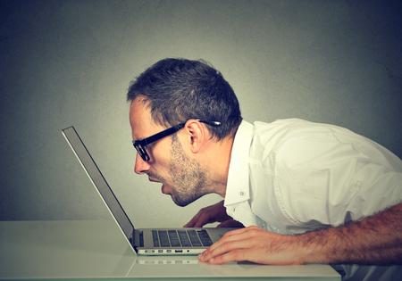 Foto de Side profile man staring closely intensely at laptop screen - Imagen libre de derechos