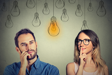 Foto de Cognitive skills ability concept, male vs female. Young man and woman looking at bright light bulb isolated on gray wall background - Imagen libre de derechos