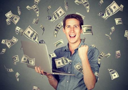 Photo pour Successful young man using laptop building online business making money dollar bills cash falling down. Money rain. Beginner IT entrepreneur success economy concept  - image libre de droit
