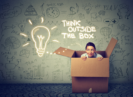Foto de Think outside the box concept. Young woman coming out of box isolated on gray info graphic wall background - Imagen libre de derechos