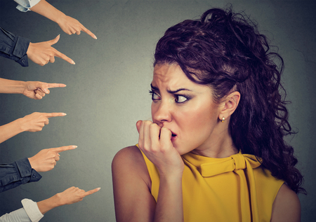 Foto de Anxious woman judged by different people fingers pointed at her. Concept of accusation of guilty girl. Negative human emotions face expression feeling   - Imagen libre de derechos
