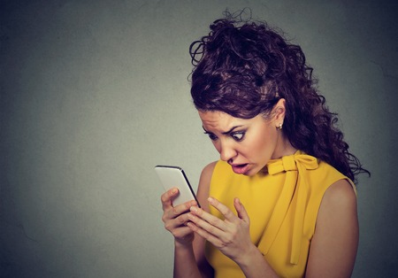 Photo pour Scared shocked young woman holding cellphone in hands looking at screen with cross face expression at stressful texts and calls isolated on gray background. Negative human emotion  - image libre de droit