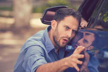Photo pour Young worried funny looking man obsessing about cleanliness of his new car on a summer day. Car care and protection concept - image libre de droit