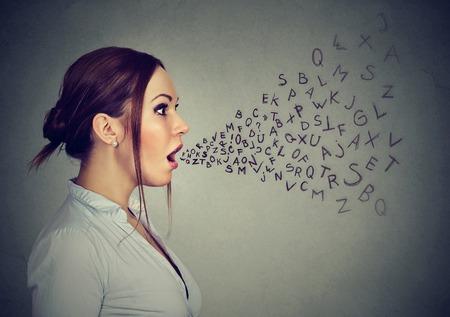 Foto de Woman talking with alphabet letters coming out of her mouth. - Imagen libre de derechos