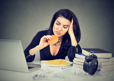 Photo pour Sedentary lifestyle and junk food concept. Tired stressed woman sitting at her desk eating hamburger and french fries   - image libre de droit
