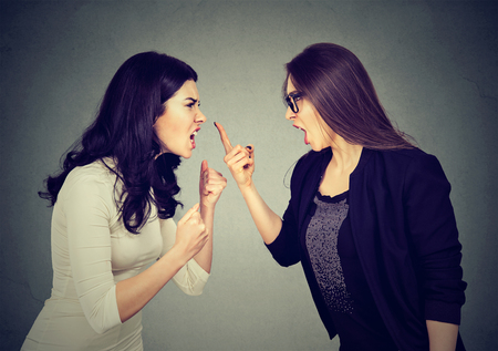 Photo pour Fight. Two women screaming at each other on gray wall background  - image libre de droit