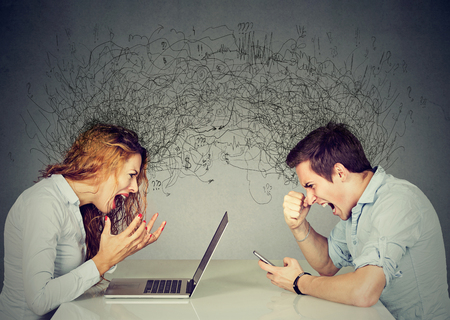 Foto de Stressed business woman screaming at laptop sitting at table across angry man shouting at mobile phone exchanging with clutter of negative thoughts and emotions. Distant relationship concept  - Imagen libre de derechos