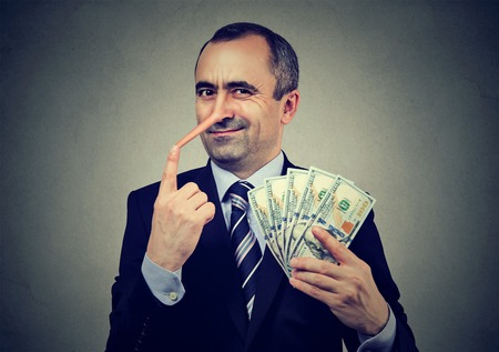 Photo for Financial fraud concept. Liar businessman with dollar cash - Royalty Free Image