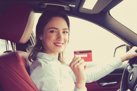Photo pour Happy woman sitting inside her new car showing credit card - image libre de droit