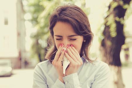 Foto de Woman with allergy symptoms blowing nose - Imagen libre de derechos