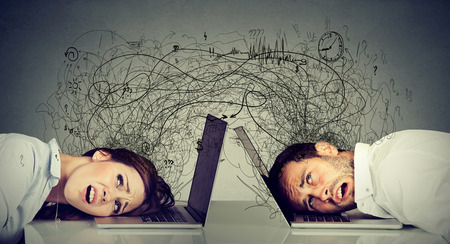 Foto de Stressed business woman and man resting head on laptop sitting at table frustrated with each other exchanging with clutter of negative thoughts and emotions. Distant relationship concept - Imagen libre de derechos