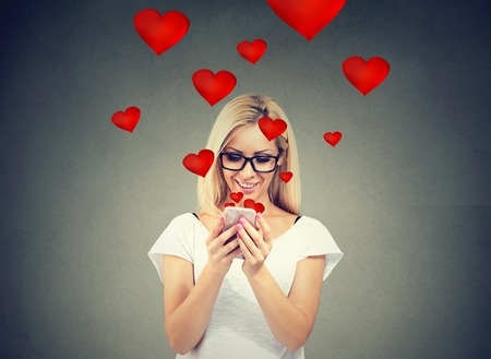 Foto de Beautiful woman sending love text message on mobile phone with red hearts flying away from screen isolated on gray background. - Imagen libre de derechos