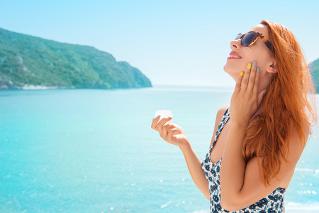 Photo pour woman applying sunscreen sunblock lotion by seaside smiling happy outdoors - image libre de droit