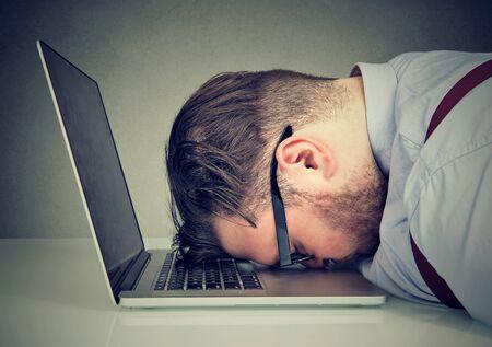 Foto de Side view of chubby man looking broken while lying on top of laptop.  - Imagen libre de derechos