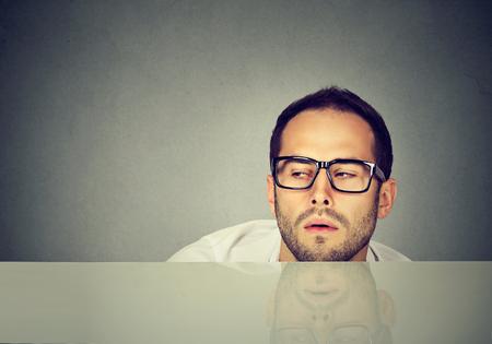 Foto de Young casual man in eyeglasses looking exhausted while working while day long.  - Imagen libre de derechos